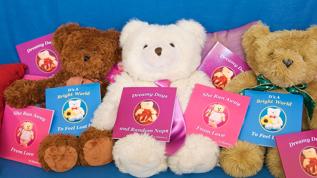 Mawson and his friends proudly display little books with lots of heart, Its A Bright World to Feel Lost In, She Ran Away From Love, and Dreamy Days and Random Naps
