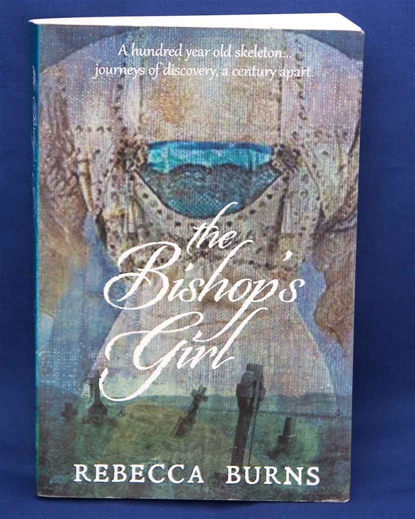 A hundred year old mystery, secret lives, torn relationships. The Bishops Girl by Rebecca Burns. Cover image shows the mystifying nurses smock that both excites and puzzles researchers for decades.